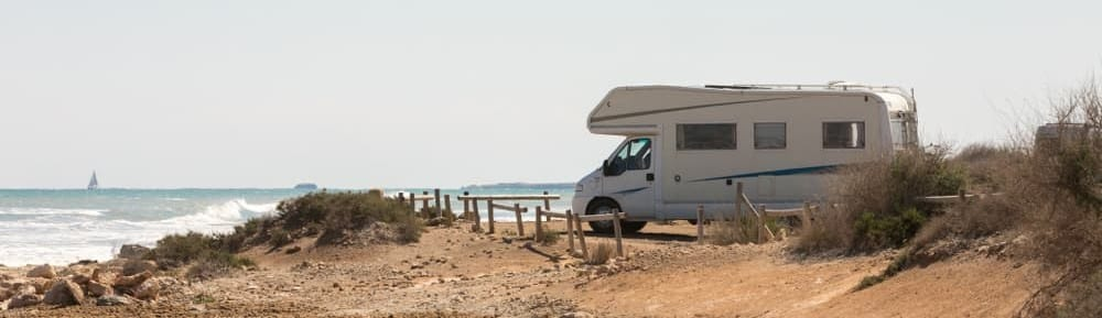 Caravan motorhome parked on the beach in front of the blue sea in a beautiful place of wild nature